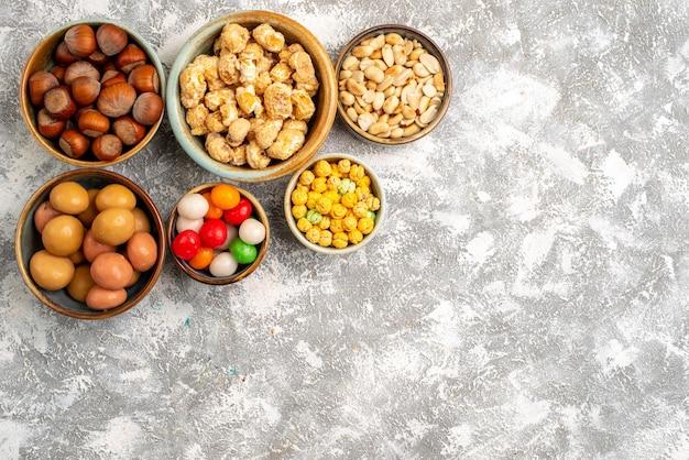 Vue de dessus des noisettes et des arachides avec des bonbons sur une surface blanche