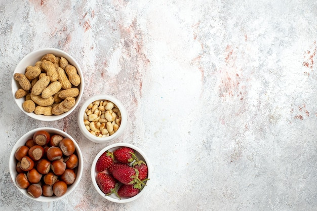 Vue de dessus des noisettes et des arachides avec des fraises sur la surface blanche