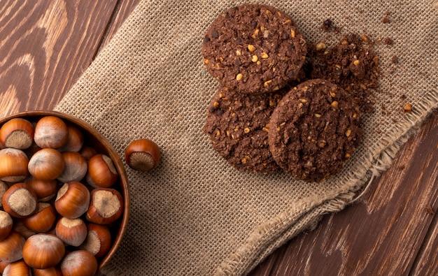 Vue de dessus de noisettes dans un bol en bois et biscuits à l'avoine sur un sac en bois