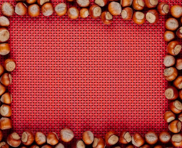 Vue de dessus des noisettes disposées avec copie espace sur fond rouge