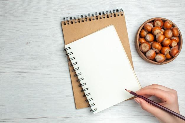 Vue de dessus des noisettes fraîches avec une femme dessinant quelque chose sur le bloc-notes sur un tableau blanc