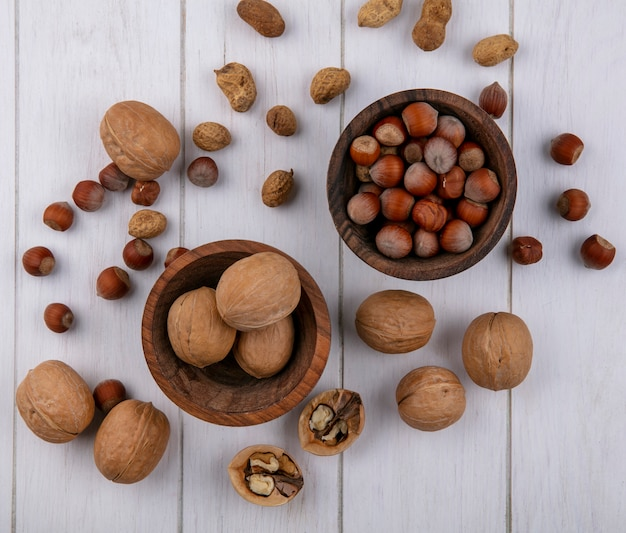 Vue de dessus des noisettes avec des noix et des arachides dans des bols sur une surface blanche