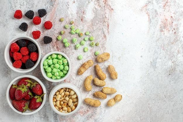 Vue de dessus des noix et des bonbons aux fraises sur une surface blanche