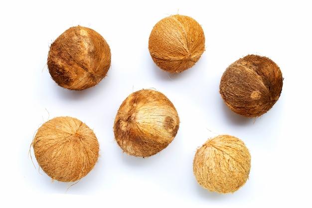 Vue de dessus des noix de coco mûres sur fond blanc.