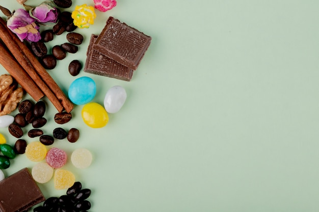 Vue de dessus des noix dans des bonbons au chocolat marmelade grains de café et des bâtons de cannelle sur la table avec copie espace