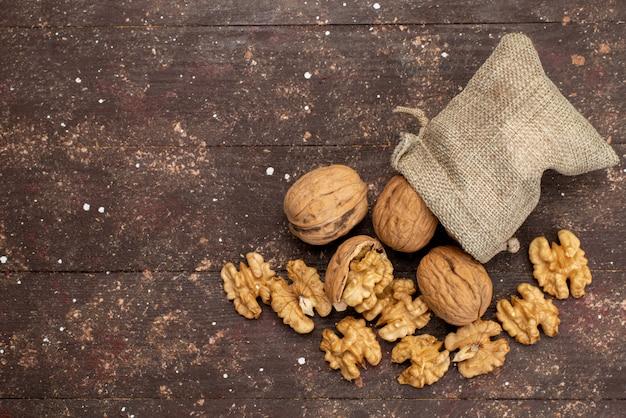 Vue de dessus des noix entières fraîches en coquilles et nettoyées sur brown