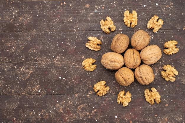 Vue de dessus des noix entières fraîches à l'intérieur de la coque et nettoyées sur bois brun