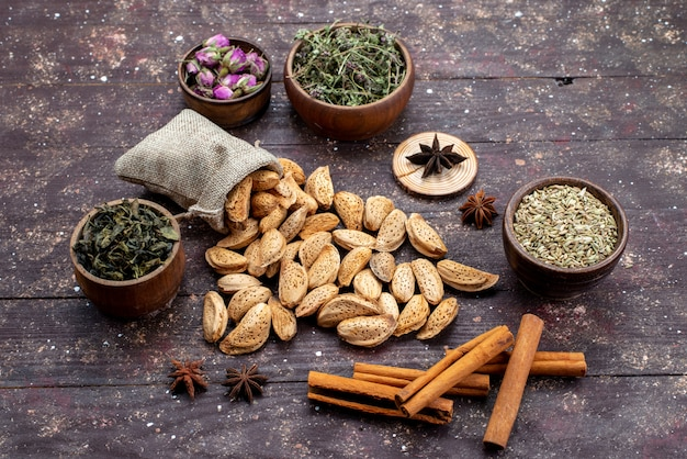 Une vue de dessus des noix fraîches salées et savoureuses avec de la cannelle sur la coque en bois foncé