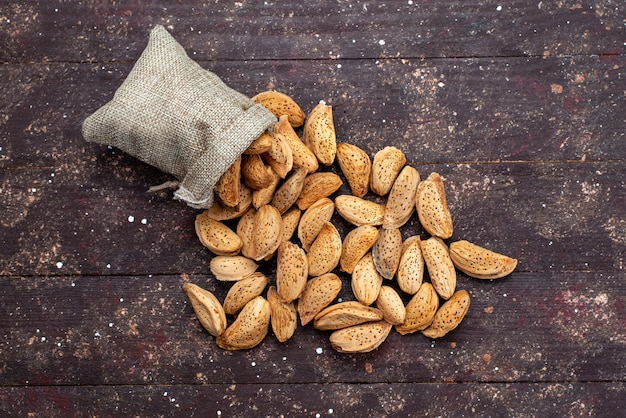 Une vue de dessus des noix fraîches salées et savoureuses sur la coquille de collation de noix de bureau en bois foncé