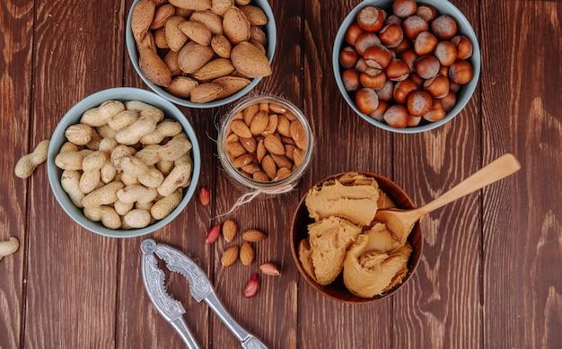 Vue de dessus des noix mélangées et un bol avec du beurre d'arachide avec un casse-noix sur fond en bois