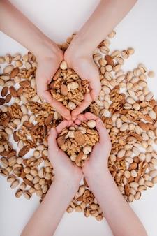 Vue de dessus noix mélangées dans les quatre mains de l'enfant noix, pistache, amandes, noisettes,