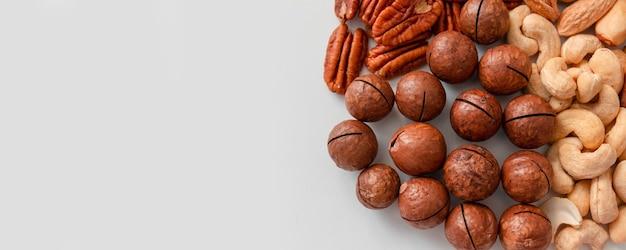 Vue de dessus des noix de pécan, des noix du brésil, des noix de cajou, des amandes et de la noix de macadamia. composition nutritionnelle appropriée de photo verticale de motif de noix assorties sur fond gris. mise à plat, place vide pour le texte