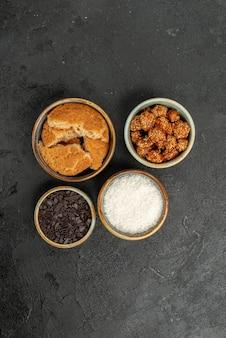 Vue de dessus des noix sucrées avec des biscuits tranchés sur une surface sombre, un thé aux bonbons aux biscuits