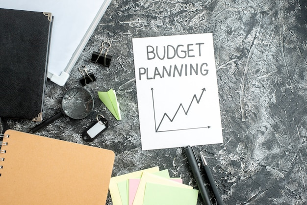 Vue de dessus note de planification du budget avec des stylos sur la surface grise cahier de travail étudiant école travail entreprise budget budget