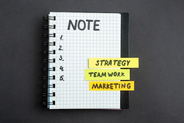 Vue de dessus des notes d'affaires de motivation avec le bloc-notes sur fond sombre succès commercial travail de direction stratégie de marketing de travail de bureau