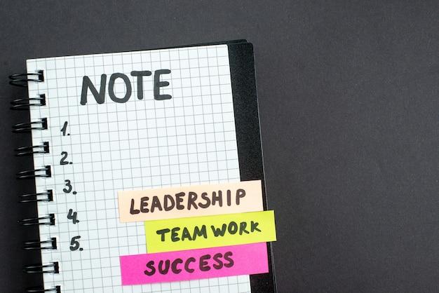 Vue de dessus des notes d'affaires de motivation avec le bloc-notes sur fond sombre travail d'affaires succès bureau de direction stratégie marketing travail d'équipe
