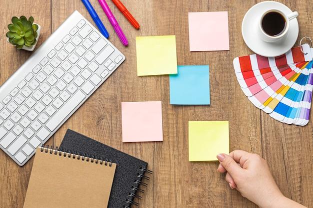 Vue de dessus des notes autocollantes avec des crayons de couleur et une palette de couleurs
