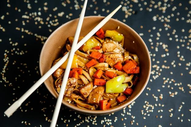 Vue de dessus des nouilles au poulet avec des légumes dans une assiette avec des baguettes et des graines de sésame sur fond noir
