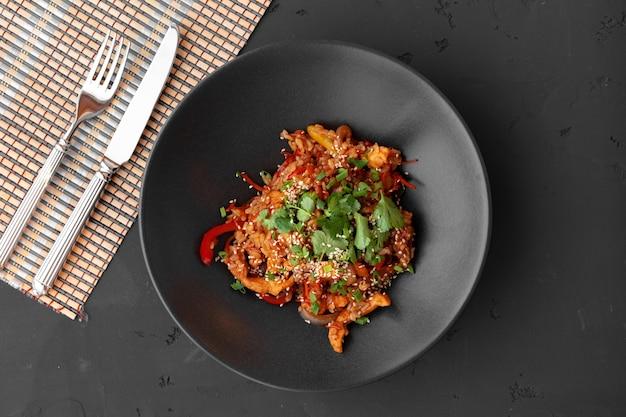 Vue de dessus des nouilles au wok avec des légumes et de la viande dans un bol sur fond gris