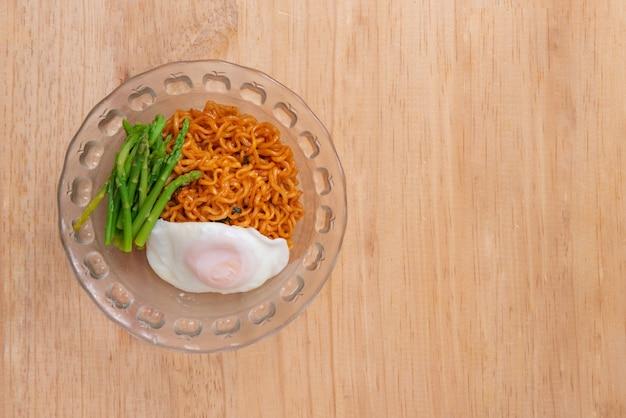 Vue de dessus des nouilles aux œufs et aux asperges sur fond de table en bois avec espace de copie
