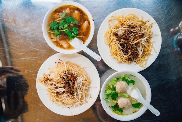 Vue de dessus des nouilles aux oeufs avec pousse servies avec du poisson en sauce et une soupe claire au porc émincé.