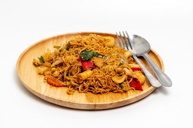 Vue de dessus de nouilles frites dans une assiette en bois ronde avec une cuillère et une fourchette