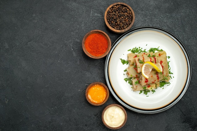 Vue de dessus nourriture appétissante chou farci à côté de bols d'herbes poivre noir sauces blanches et jaunes épices riz et crème sure sur table sombre