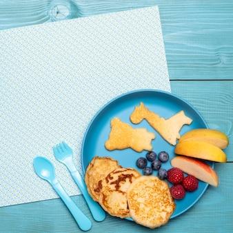 Vue de dessus de la nourriture pour bébé sur une assiette avec des pommes et des framboises