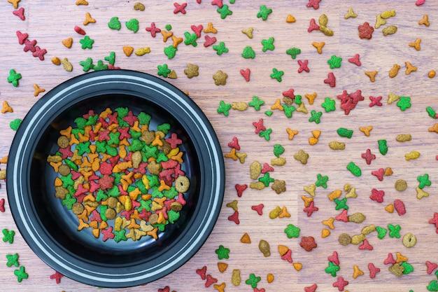 Vue de dessus de la nourriture sèche pour chat dans un bol sur fond de bois