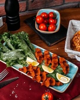 Vue de dessus de la nourriture turque cig kofte au citron et laitue sur une table en bois