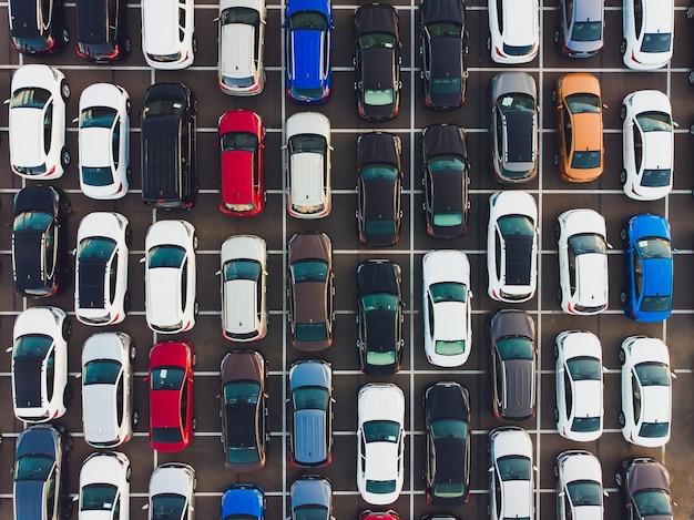 Vue de dessus de nouvelles voitures alignées à l'extérieur d'une usine automobile pour l'importation et l'exportation.