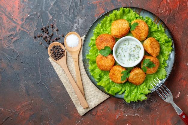 Vue de dessus nuggets de poulet fourchette sur assiette sel et poivre noir dans des cuillères en bois sur table sombre