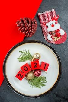 Vue de dessus des numéros d'accessoires de décoration sur une assiette et un cône de conifère chaussette de noël sur une table sombre