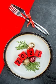 Vue de dessus des numéros d'accessoires de décoration sur une assiette et des couverts sur une table sombre