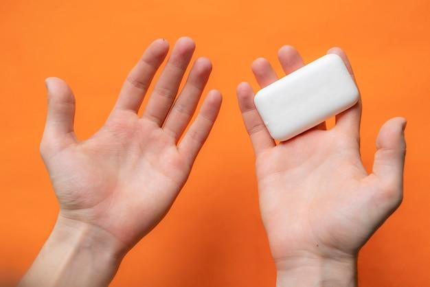Vue de dessus o mains tenant une barre de savon, concept d'hygiène isolé