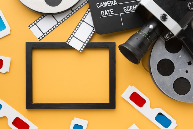 Vue de dessus des objets de cinéma sur fond jaune avec cadre noir