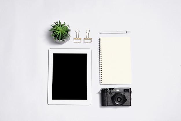 Vue de dessus ocamera, bloc-notes avec stylo et ordinateur portable à écran blanc sur fond blanc