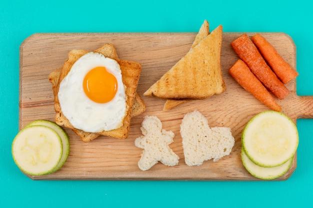 Vue de dessus de l'oeuf au plat avec des toasts et des légumes sur la surface bleue horizontale