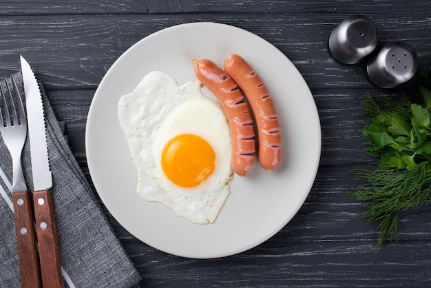 Vue de dessus de l'oeuf du petit déjeuner et des saucisses sur une plaque avec des herbes