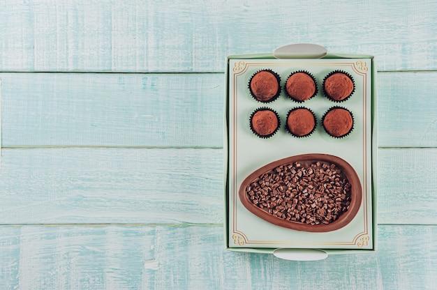 Vue de dessus de l'oeuf de pâques au chocolat brésilien dans une boîte-cadeau avec des bonbons au chocolat trufas - ovo de chocolate de colher