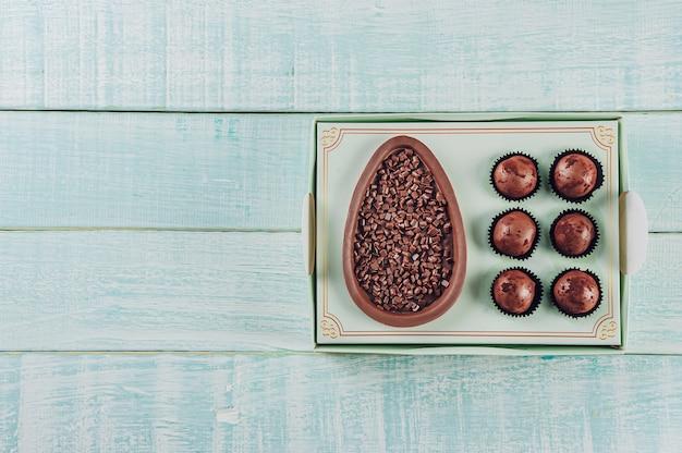Vue de dessus de l'oeuf de pâques au chocolat brésilien dans une boîte cadeau avec des bonbons brésiliens brigadeiro - ovo de chocolate de colher