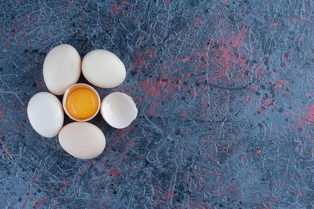 Vue de dessus d'un œuf de poule blanc frais cassé avec du jaune et du blanc d'œuf.