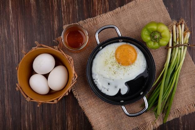 Vue de dessus des œufs au plat dans une poêle avec du miel, des oignons verts, des poivrons et des œufs de poule dans un panier sur un fond en bois