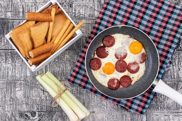 Vue de dessus des œufs au plat avec des toasts sur une surface blanche horizontale