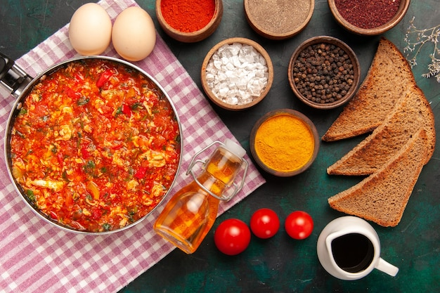 Vue de dessus des œufs brouillés avec des tomates et différents assaisonnements sur le fond vert foncé