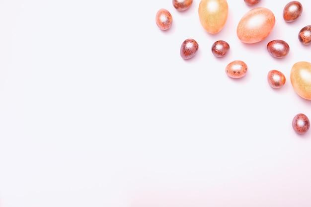 Vue de dessus des oeufs de couleur pastel de pâques sur une surface blanche