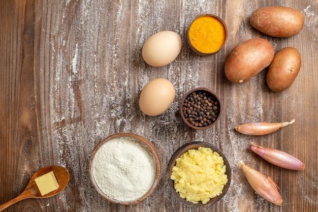 Vue de dessus des œufs crus avec des assaisonnements de légumes et de la farine sur un bureau en bois de la pâte de farine crue