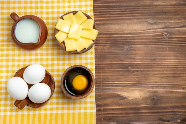 Vue de dessus des œufs crus avec du fromage et du lait sur une surface en bois des œufs de produit de la pâte repas alimentaire cru