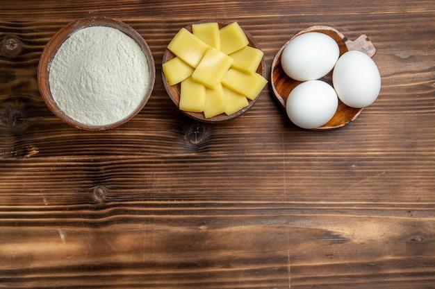 Vue de dessus des oeufs crus entiers avec de la farine et du fromage sur la table brune oeufs pâte farine produits de poussière