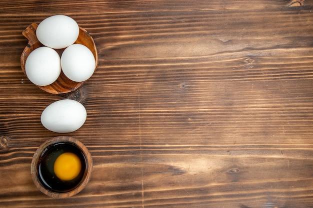 Vue de dessus oeufs crus entiers sur fond en bois brun repas petit déjeuner alimentaire oeuf en bois